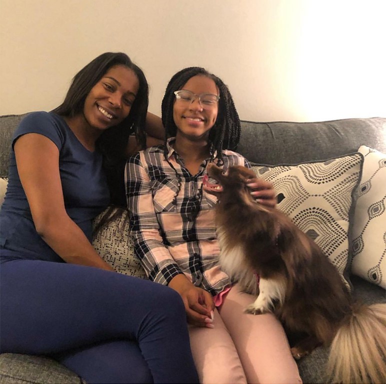 photo featuring Keirra, her daughter, and their little brown and white fluffy dog sitting on a gray couch