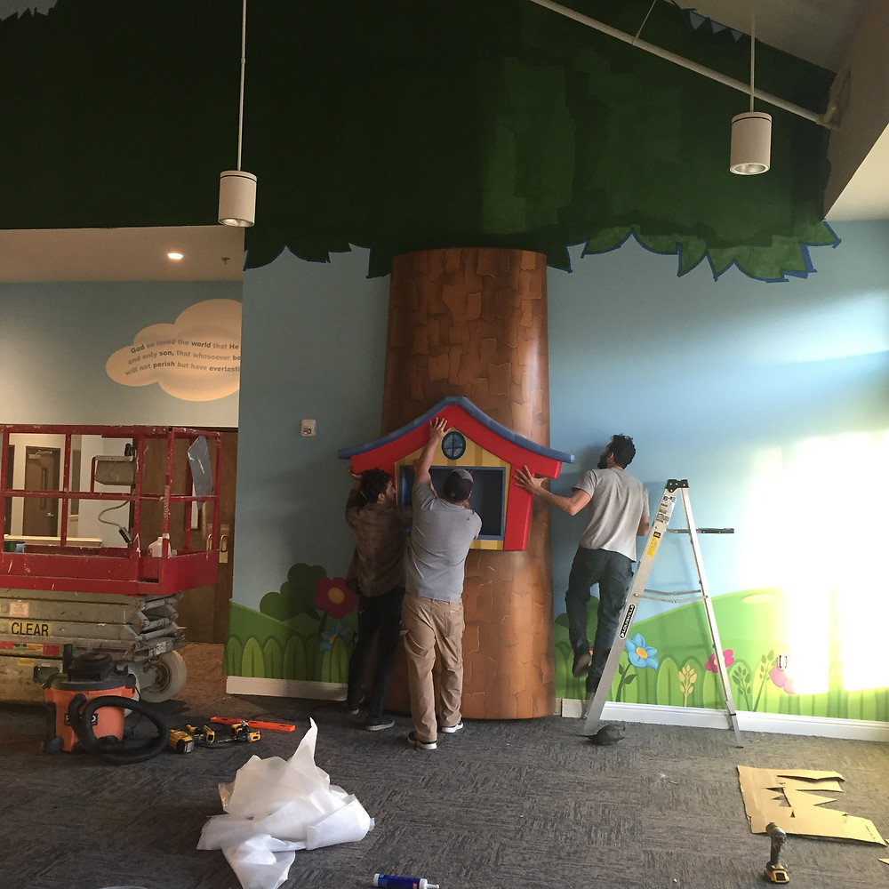 It's happening! The WOW design team installing The Nest children's area