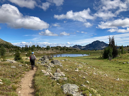 Hiker walking with a mountain view and lake in background in Pasayten Wilderness.