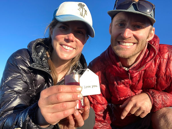 Two hikers holding up a summit register that says I Love You on it.