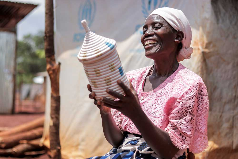 Refugee artisan admiring her product