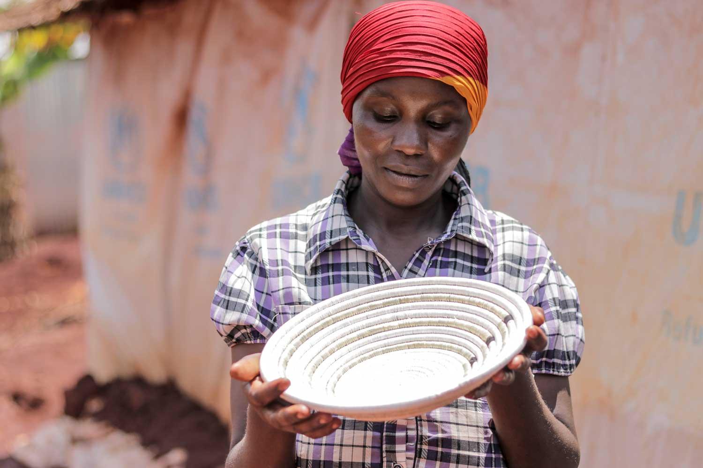 Refugee artisan admiring product