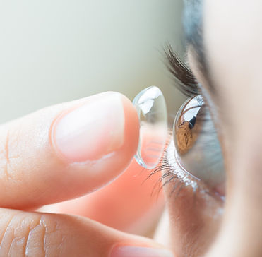 Young woman putting contact lens in her