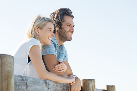 Happy young couple leaning over fence an