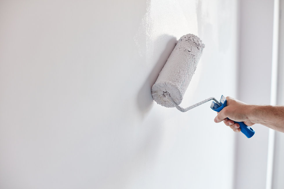 Male hand painting wall with paint rolle