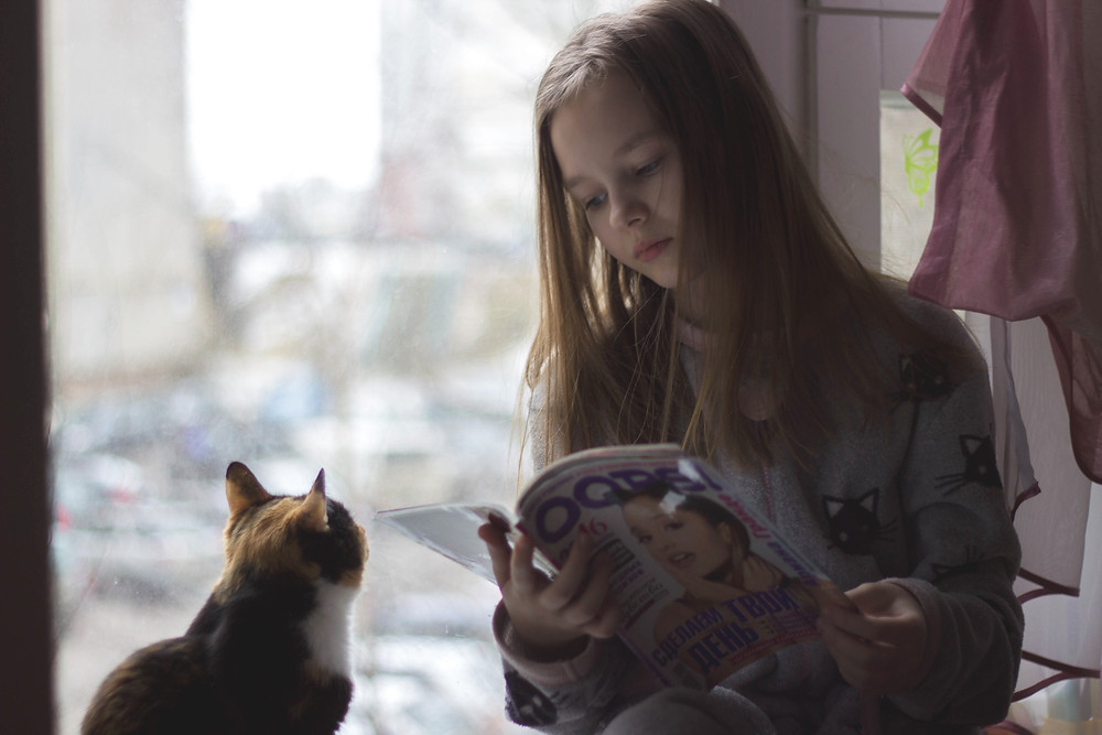 Child reading with a cat - TassieCat
