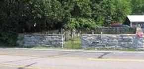 Stoner cemetery surrounded b a stone fence.