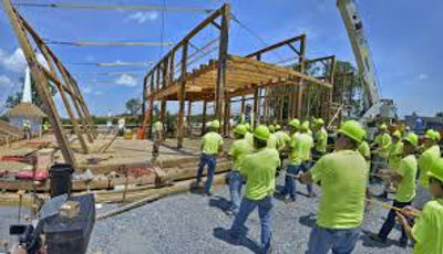 Workers helping to raise the sides of the Star Barn in its new location at Iron Stone Ranch.
