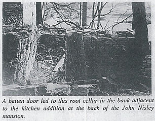 Photo of a batten door leading to the root cellar at the back of John Nisley's mansion.
