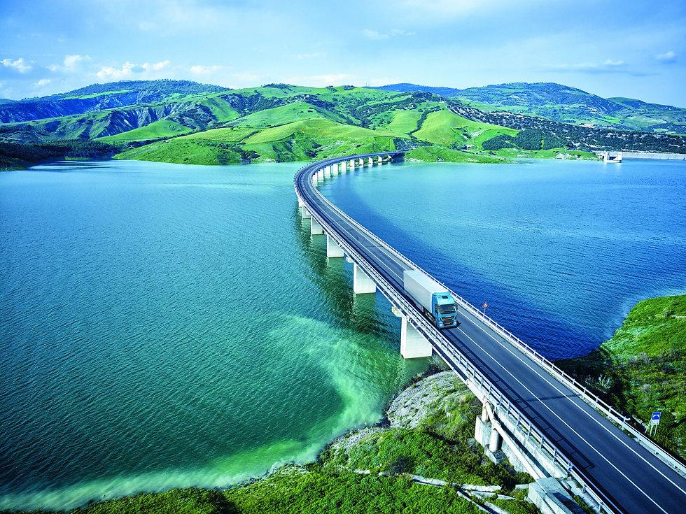 Landschaftsbild mit einer Fahrzeugbrücke die über einen Fluss führt