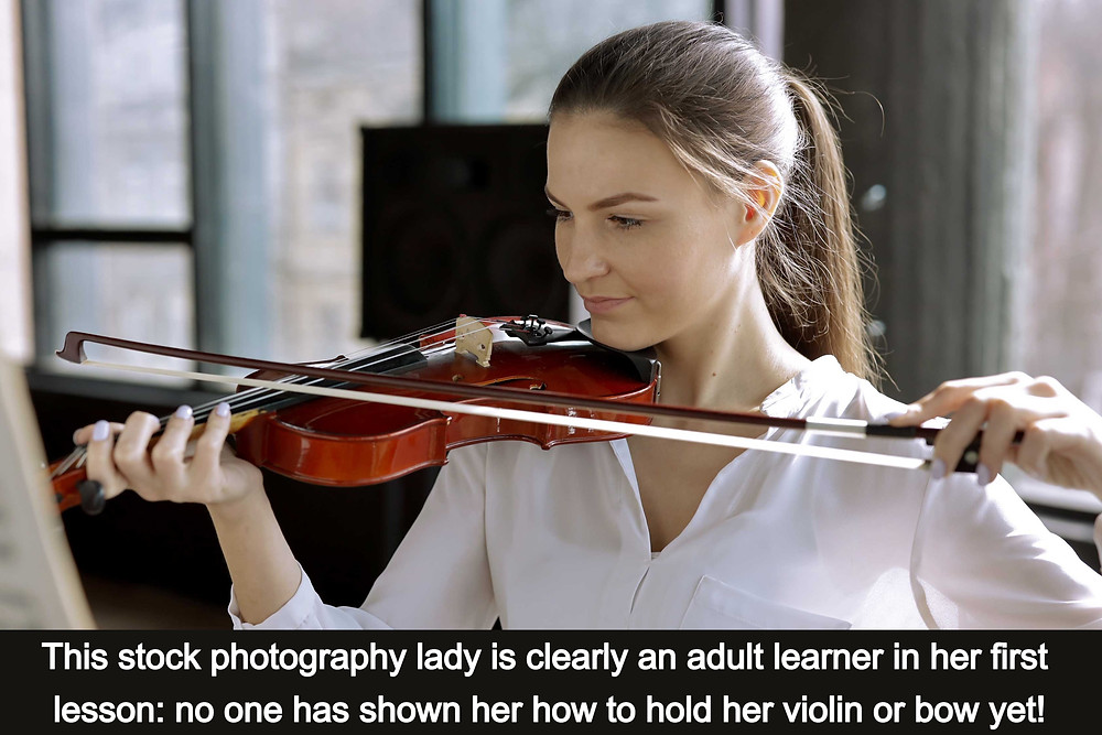 A woman holding a violin on the wrong shoulder and incorrectly!