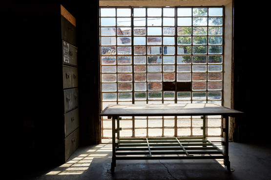 Tavolo a due ripiani con vetrata industriale sul fondo