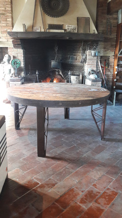 Tavernetta rustica con tavolo rotondo e camino acceso