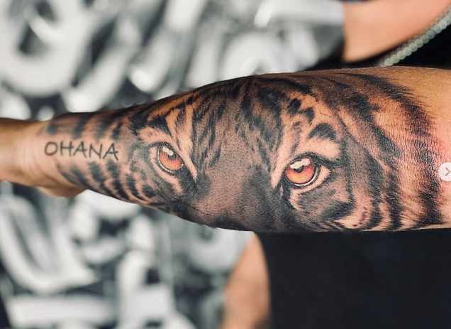 realistic black and grey tiger eyes on forearm
