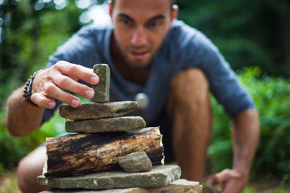 focused man outside carefully balancing rocks as cairn