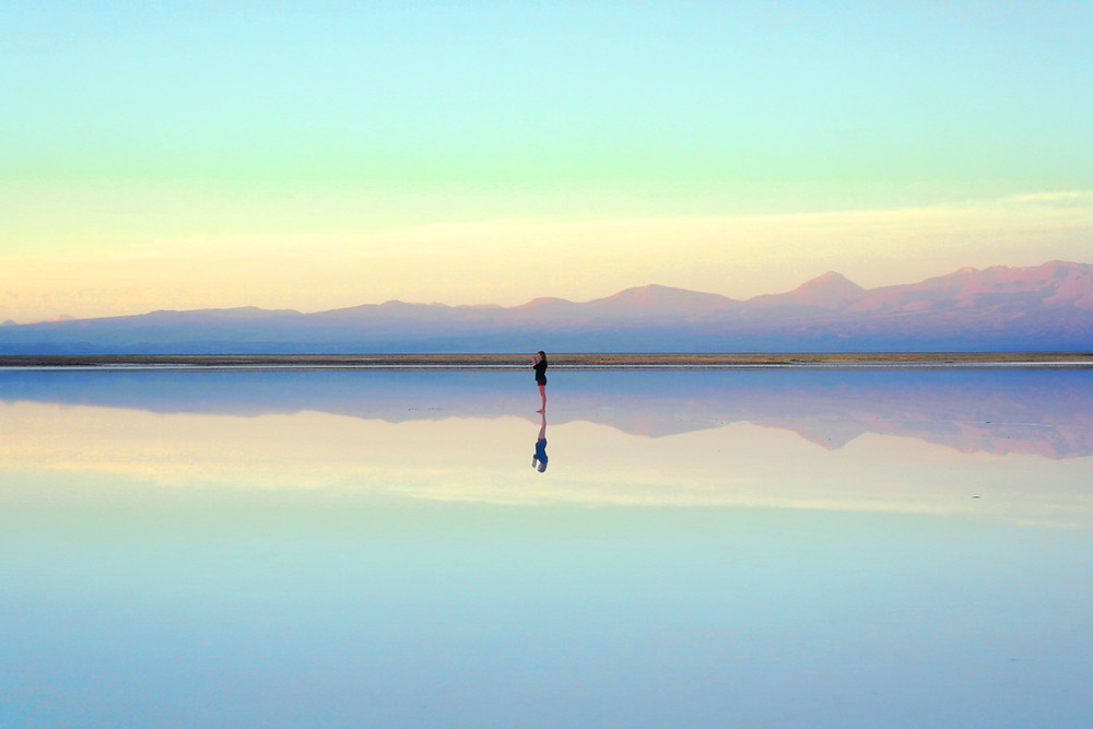 woman standing on water reflecting mountains in the distance at sunrise