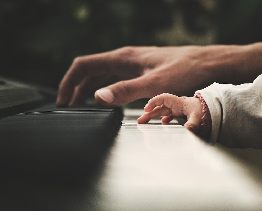 Doing for others: hand of an adult and hand of a baby playing piano