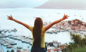 a happy woman with arms outstretched on the top of a hill overlooking water and mountains