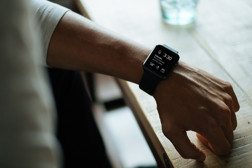 man's apple watch showing time and calendar