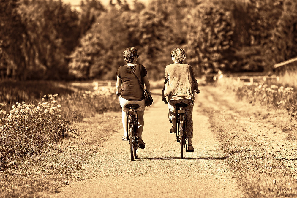 mature women riding bikes together and talking