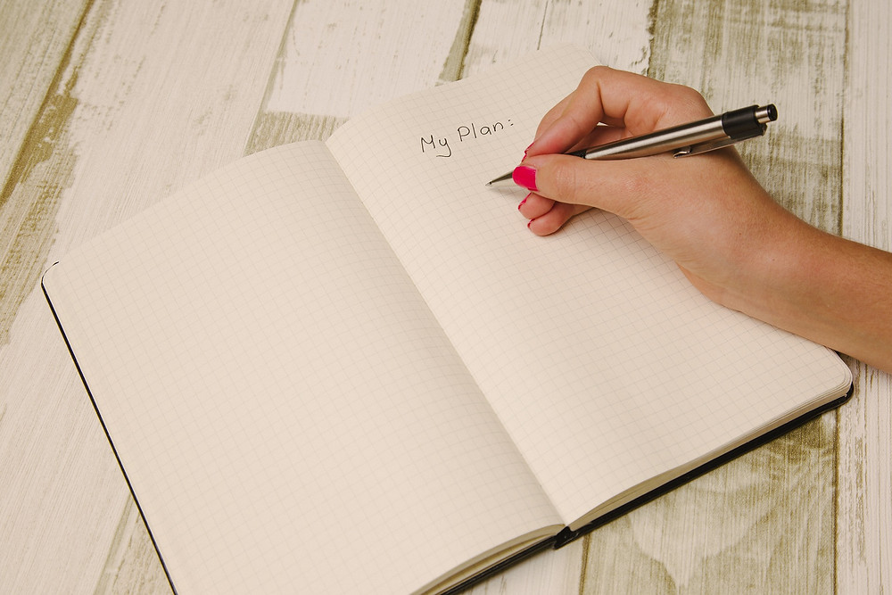a woman's hand holding a pen writing her plans down in a notebook