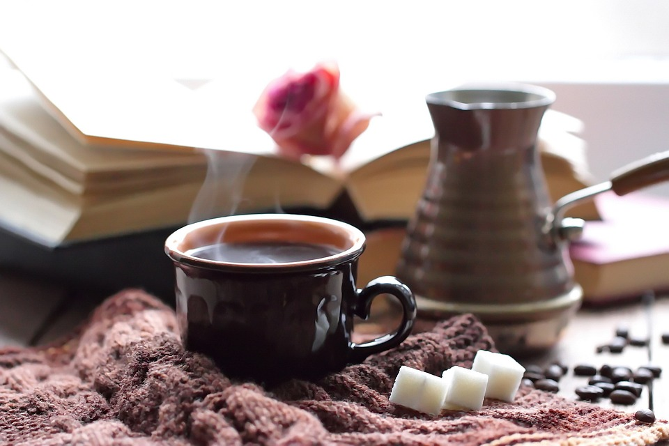 a mug of coffee with a knit sweater, sugar cubes, a book and a rose