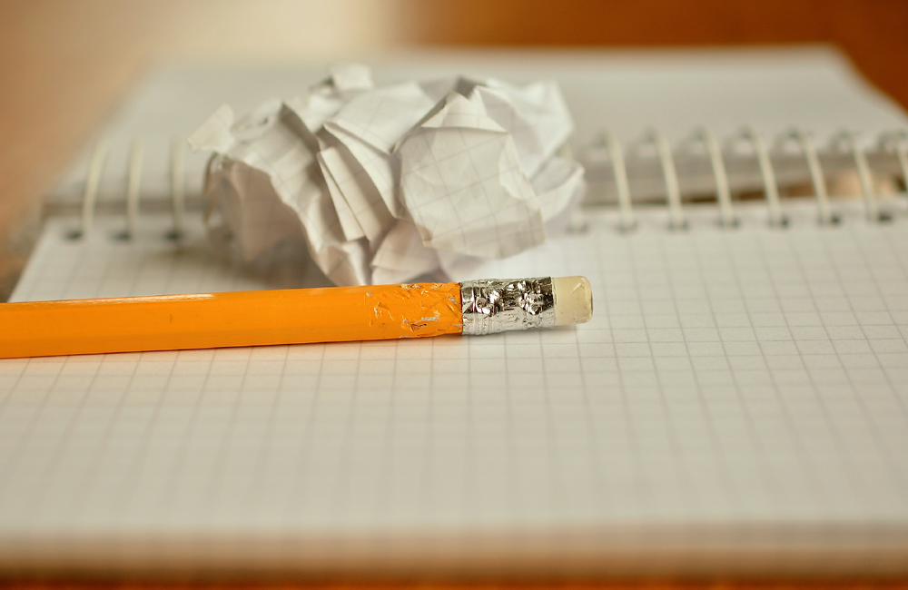 chewed end of a pencil on top of a notebook with crumpled paper