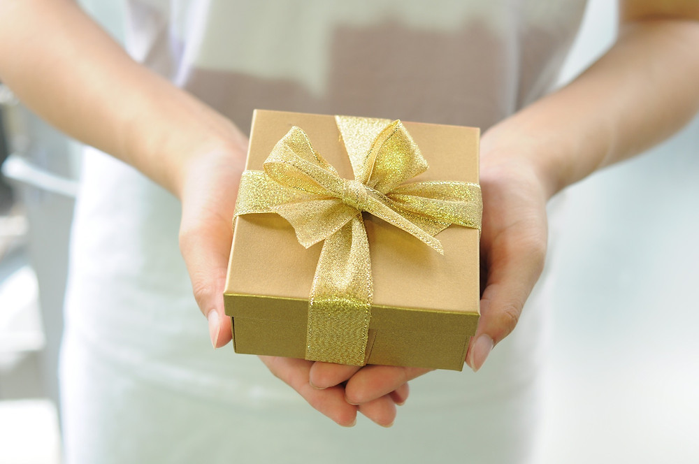 Hands holding a gold gift box as a reward for behavior