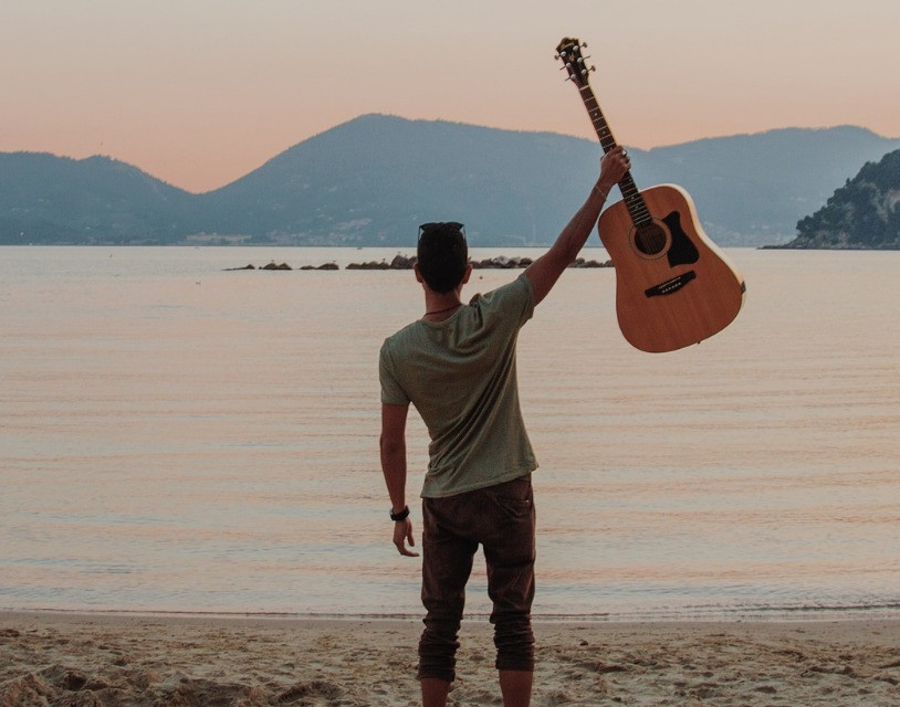 man holding a guitar by a lake triumphantly