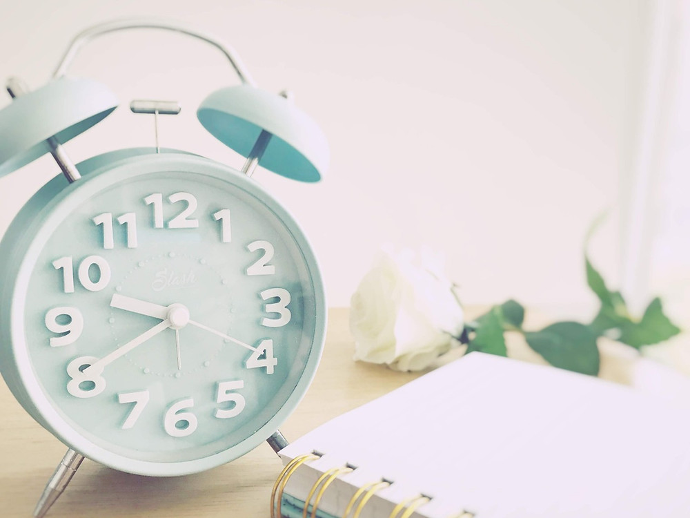 Time management and productivity image of an analog clock, notebook, and flower