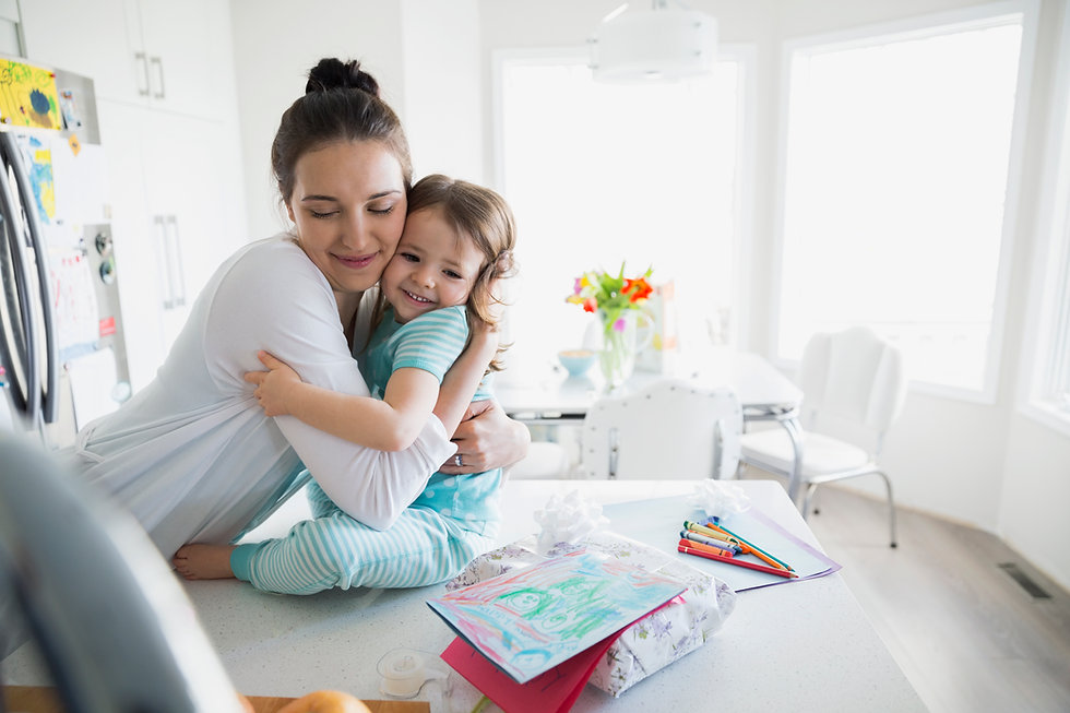 A happy mom and baby hugging in a white bright kitchen after it was cleaned by the best eco-friendly house cleaning services in Kelowna and West Kelowna.