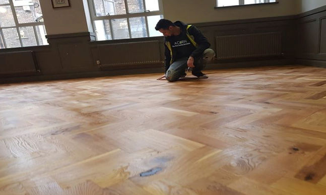 Inspecting a floor befroe applying the final coat of floor varnish