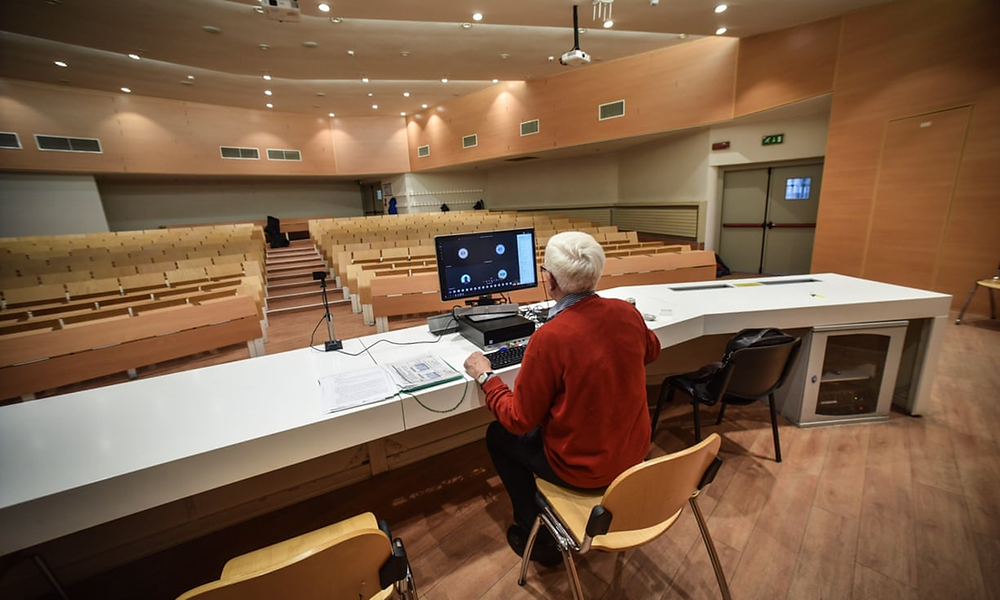 A college professor holds an online lecture from an empty classroom in Milan.