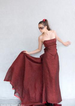 Abito cangiante nero e rosso in organza con stampe di rose.