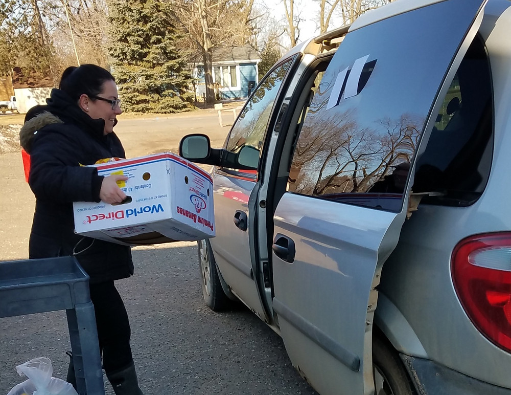 A Mora Food Pantry volunteer delivers pre-packaged items to a client.