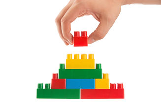 Hand Building Up A Wall By Stacking Up L