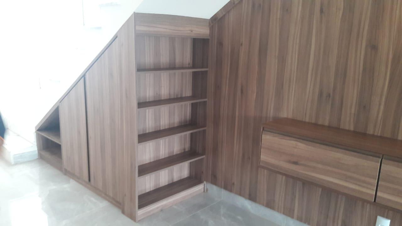 Aproveitamento total do espaço abaixo da escada, com um armário de duas portas e nichos laterais.