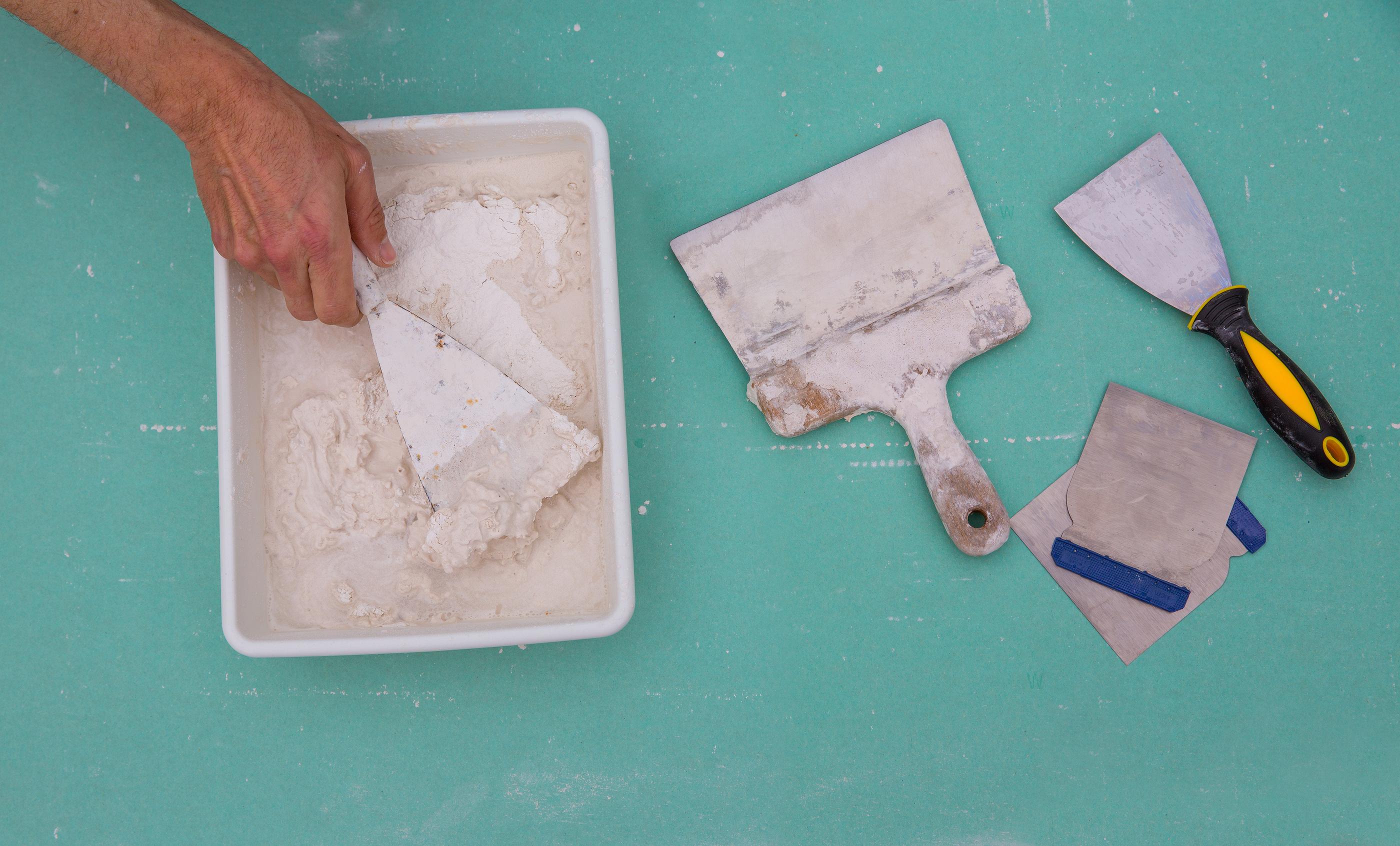 Plastering tools for plaster like plaste trowel spatula on green drywall plasterboard