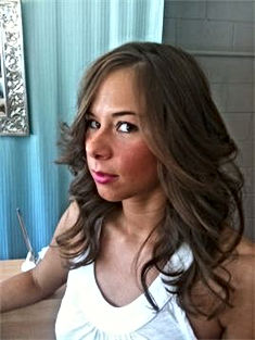 A brunette woman with a rockstar haircut done by Serena.