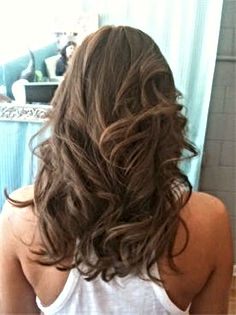 A brunette woman with a rockstar haircut with scattered layers.
