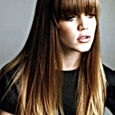 Woman with long, straight, ombre hair and fringe modeling.