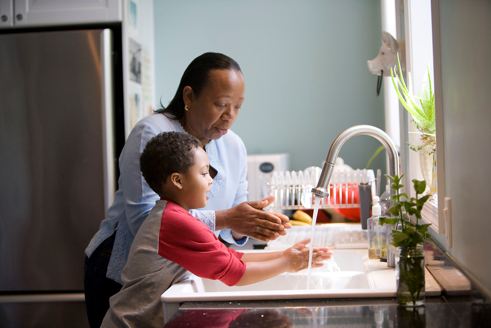 Woman and little boy washing their hands together