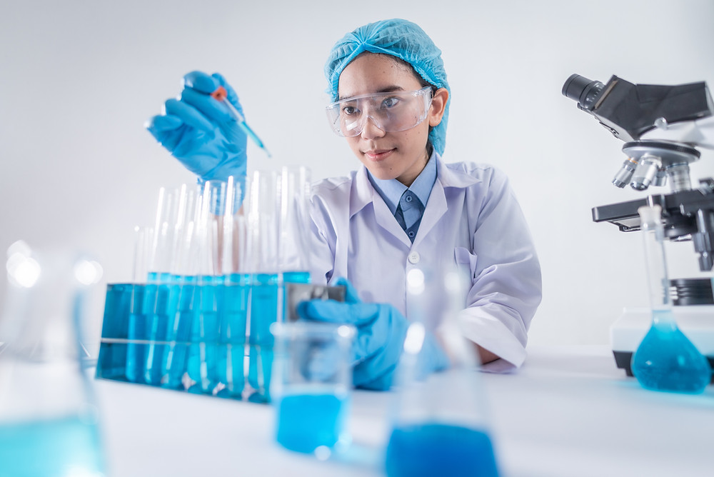 Woman in lab pinching liquid into test tubes