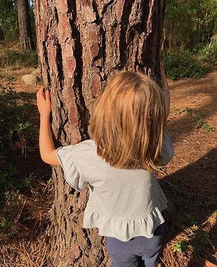Criança abraça árvore nas atividades para famílias da Hearts into Nature