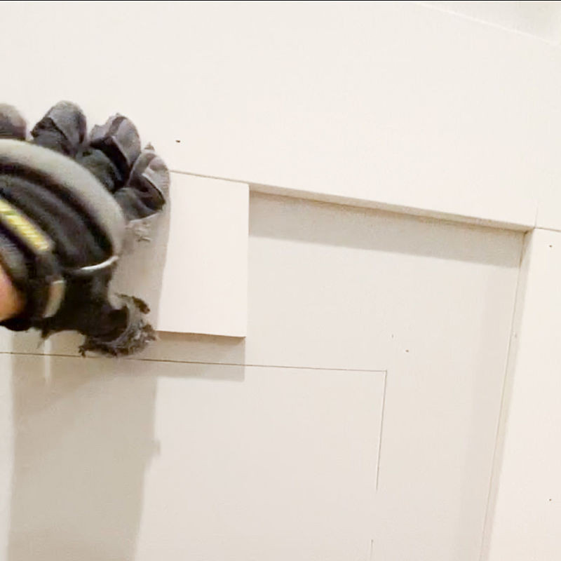 Use a block to keep spacing uniform when attaching trim to a feature wall