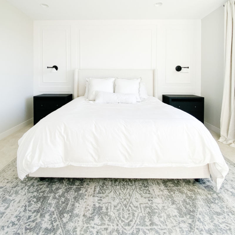 DIY bedroom makeover reveal with DIY feature accent wall, white bedding duvet, black wall sconces and black night stands.