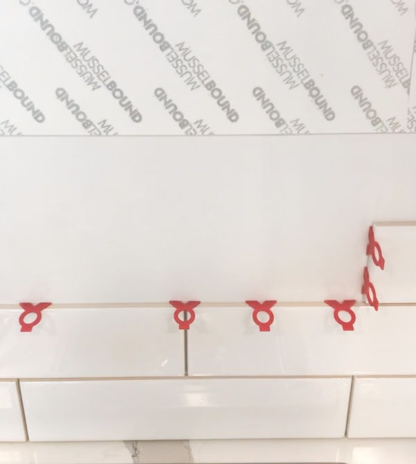 Using spacers to adhere the backsplash tile to the adhesive like a pro