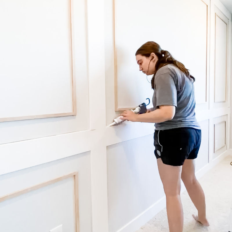 Caulking trim seam for feature wall in bedroom makeover
