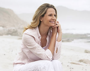 Happy woman dressed all in white sitting