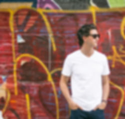 Young man standing next to a wall covere